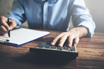 Businessman hand calculator and document
