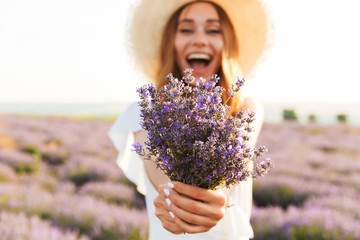 Cheerful young girl in straw hat holding lavender bouquet