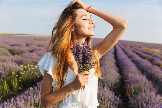 Photo of pretty european woman in dress holding bouquet with flowers, while walking outdoor through lavender field in summer