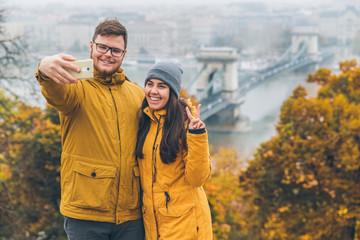 couple taking selfie old chain bridge cross danube river on background. budapest, hungary