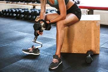 Cropped image of european disabled invalid woman wearing prosthesis in tracksuit, training and lifting dumbbell in gym