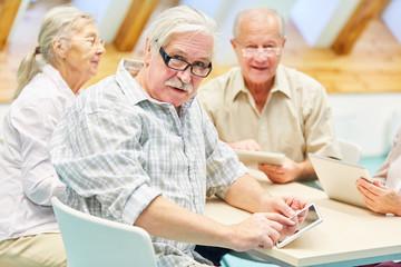 Senior Mann voll Neugier im Computerkurs