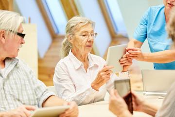Pflegekraft hilft einer Seniorin mit Tablet PC