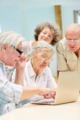 Senioren Gruppe arbeitet konzentriert mit Laptop