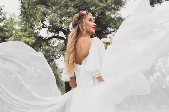 low angle view of happy blonde bride in wedding dress and floral wreath looking away in park