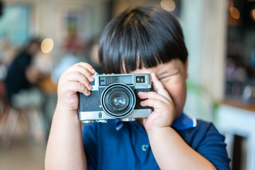 A boy is taking a Photo film camera.