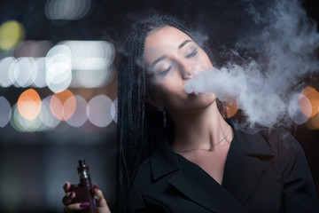 Woman smoking e-cigarette against night city lights background