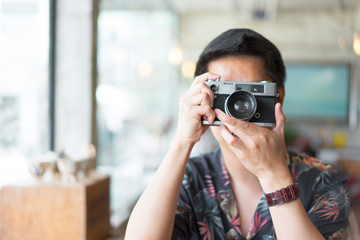 A hipster teenager is taking a film camera in the cafe.