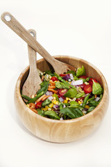 Pasta salad in a wooden bowl with wooden salad utensils