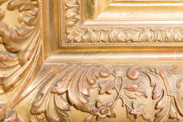 close up of rustic baguette of the painting. gold carved flowers and leaves