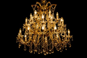 Luxury interior chandelier has light candles and dark background. Noble candelabra hanging on ceiling with lots of little gems. Premium decoration for palace gala, villa business meeting or wedding