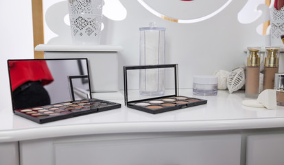 There are different powders and palettes with eye shadows on a table in a make up studio.