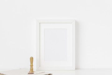 Stylish white a5 portrait frame mockup with gold stamp and printing on white wall background. Empty frame, poster mock up for presentation design. Template frame for text, lettering, modern art.