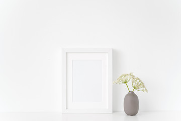 Minimal white portrait a5 frame mock up with a Aegopodium in gray vase. Poster Mockup for quote, promotion, headline, design. Template for small businesses, lifestyle bloggers, social media