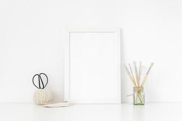 Elegant white frame portrait mockup A4 in interior with vintage elements. Frame mock up background for poster frame for social media, lettering, art and design. Indoor, frame on table. Back to school.