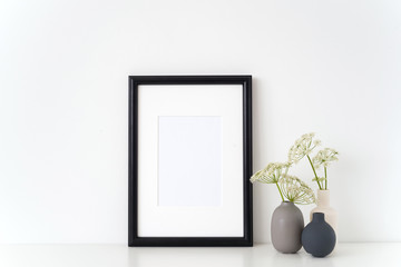 Black portrait frame mock up with a summer Aegopodium podagraria in little vases gray, white and black. Mockup for quote. Template for small businesses, lifestyle bloggers, social media