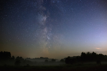 Starry night sky in the northern hemisphere. View of the Milky Way over a meadow with fog. Long exposure.