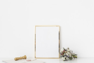 Gold a4 portrait frame mockup with small bouquet of dried flowers and gold stamp on white wall background. Empty frame, poster mock up for presentation design.