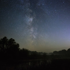 Starry night sky in the northern hemisphere. View of the Milky Way over a lake with a mist. Long exposure.