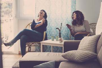 two young happy women friends sit down at home and laugh telling stories and facts about the day. indoor lifestyle concept in friendship with ladies using phone and internet to share adventures