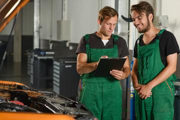 Two mechanics read the technical documentation near the car