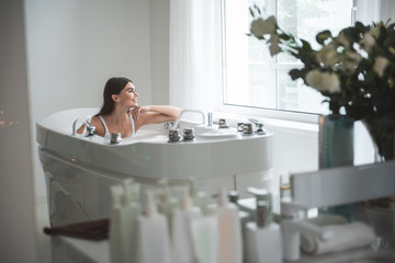 Side view optimistic lady with attractive smile dreaming while looking at window in room. She leaning chin on hand. Glad girl having leisure in bath concept