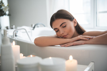 Portrait of serene female leaning on side of bath while resting there. Calm lady having leisure during spa procedure concept