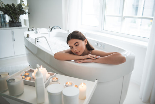 Portrait of calm girl with closing eyes having leisure in water with foam opposite candles in apartment