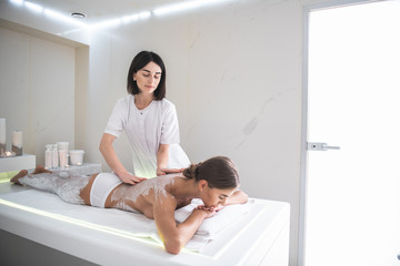 Nice rest. Serene beautiful girl lying on massage table and having back massage with cosmetic mask