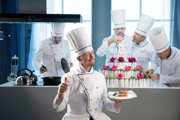 A team of cooks preparing a huge cake for the celebration