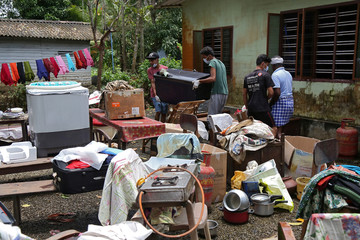 Volunteers collect household items in the lawns of a residential house before cleaning the house following floods in Kuttanad