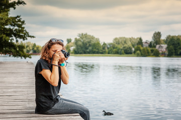 Happy woman photographer holding professional digital camera and taking photo near the lake in  park