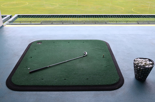 A golf course: carpets, golf clubs and baskets with golf balls set for golfing