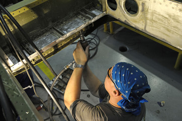 Fitter works with a screwdriver preparing the body plane for further riveting