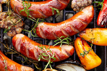 Grilled sausages and vegetables with addition spices and fresh herbs on a grill plate, top view