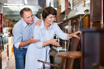 Man with wife are satisfied of furniture in antique shop