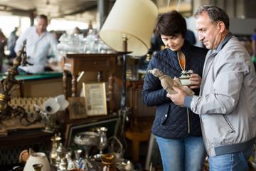 cheerful mature spouses buying retro handicrafts on flea market