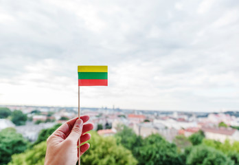 A small Lithuanian paper flag in a woman's hand against a background of a blurred city, the capital of Lithuania Vilnius, welcome to Lithuania