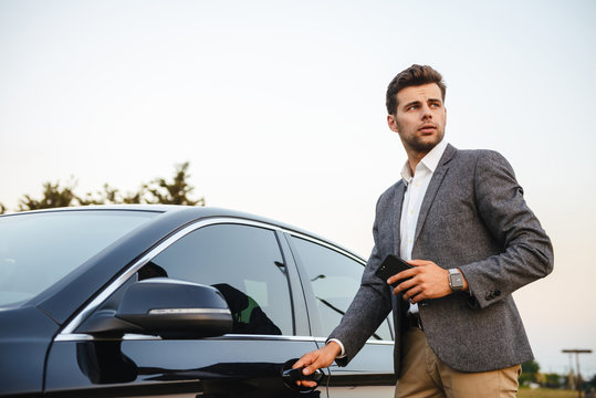 Confident young businessman in suit opens his car