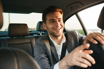 Smiling young business man passenger showing taxi driver Wall mural