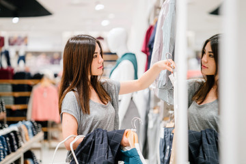 A young Japanese Asian woman is enjoying herself shopping in a clothing store. She looks serious about picking her new clothes.