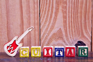 Letter Block In Word Guitar on wood  Background