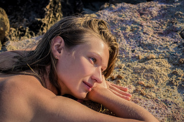 Young woman with wet hair sunbathing on stones