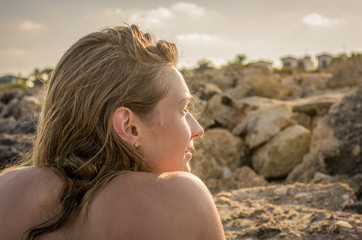 Portrait of a young pensive woman with wet hair sunbathing at sunset