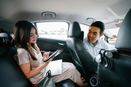A young attractive Japanese woman is reading an eBook on her tablet. She is doing this while on her way to work while riding a car which she booked via a ride hailing app.