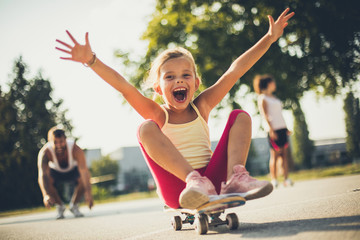 Little girl on skateboard . Parents behind.
