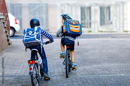 c0482a0cff0 Two school kid boys in safety helmet riding with bike in the city with  backpacks. Happy children in colorful clothes biking on bicycles on way to  school.