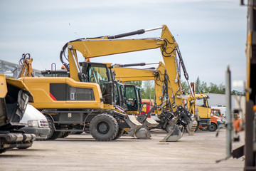 Multiple cars, excavators, trucks, loaders, concrete mixers and construction machinery in large parking lot in industrial territory, next to concrete and asphalt factory