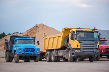 Multiple cars, trucks, loaders, concrete mixers and construction machinery in large parking lot in industrial territory, next to concrete and asphalt factory. Raw material heaps, gravel in background