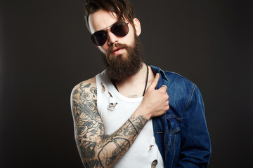 Hipster bearded boy in jeans coat and glasses